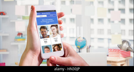 Hand holding smartphone against view of office interior with sticky note on window - Stock Photo