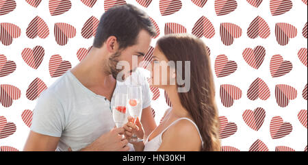 Young couple looking each other against background with hearts - Stock Photo