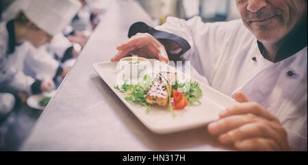 Head chef happy with finished salmon dish with trainees working in kitchen - Stock Photo