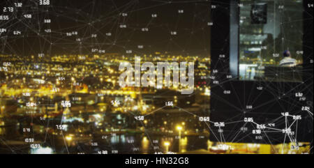 Screen with times against illuminated city against sky at night - Stock Photo