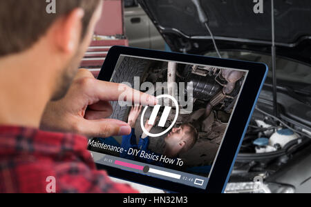 Man using tablet on wooden table against mechanic under car in garage - Stock Photo