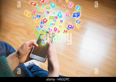 Colourful computer applications against cropped image of woman sitting on floor while using her phone - Stock Photo