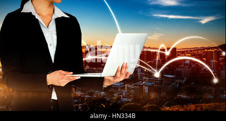 Cropped image of businesswoman holding laptop computer against beautiful view of city skyline - Stock Photo