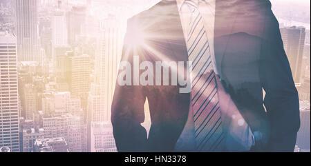 Businessman against sunrise over mountains - Stock Photo