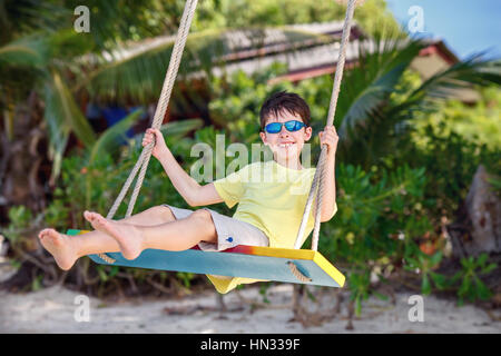 Cute boy having fun swinging at tropical island beach, Koh Samui island. Thailand, Asia - Stock Photo