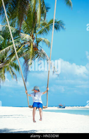 Cute boy having fun swinging at tropical island beach, Koh Phangan island. Thailand, Asia - Stock Photo