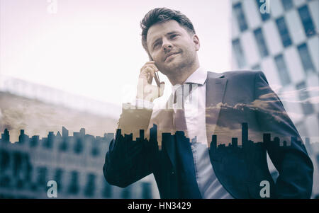 Low angle view of smart businessman talking on mobile phone against office building - Stock Photo