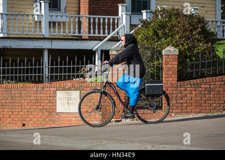 An Amish lady on a bicycle in Berlin, Ohio, USA. - Stock Photo
