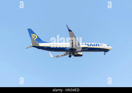 Plane Boeing 737, of Ryanair airline. Low cost travels. Blue sky. Sunny day of spring. - Stock Photo