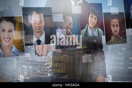 Businessman presenting profile pictures on digital interface - Stock Photo
