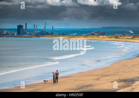 A family enjoy a beautiful beach with heavy industry in the background. - Stock Photo
