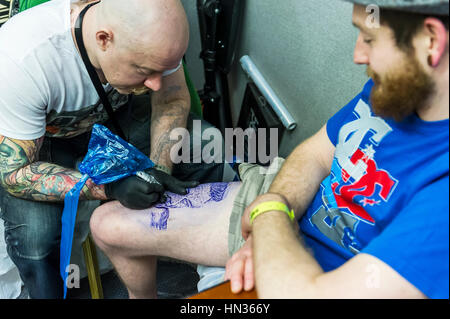 A man being tattooed on his leg. - Stock Photo
