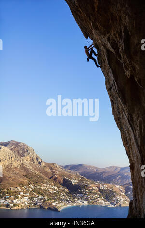 Young man climbing along rocks - Stock Photo
