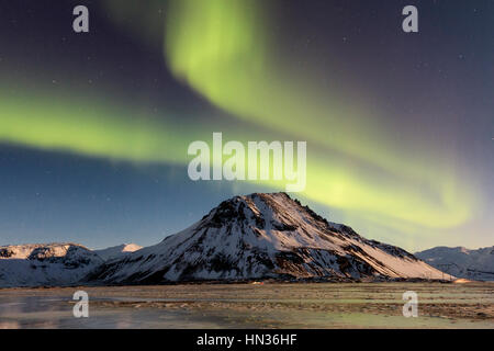 Northern lights over a mountain near Vestrahorn in Iceland - Stock Photo