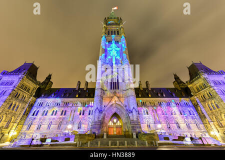 Winter holiday light show projected at night on the Canadian House of Parliament to celebrate the 150th Anniversary - Stock Photo