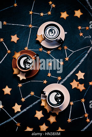 High angle shot of three cups of coffee on a dark background with some scattered star-shaped cookies and chalk drawings - Stock Photo