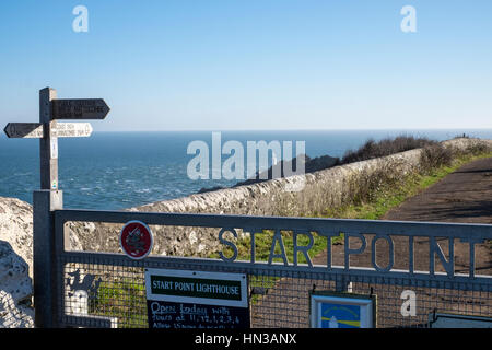 Start Point, Devon.  Stretch of coastline on the South West Coast Path. Signpost and view of the lighthouse - Stock Photo