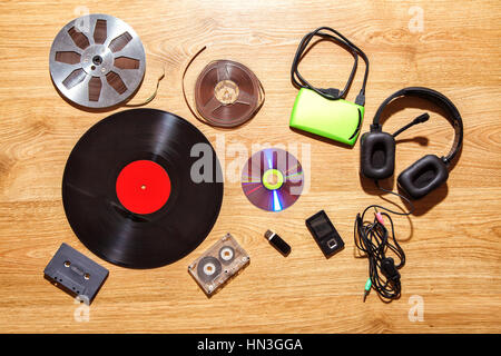 set of retro and modern audio carriers lying on hte wooden floor - Stock Photo