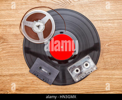 vinyl record with cassetes and reel tape lying onthe floor - Stock Photo