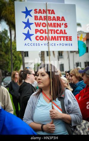A demonstrator carrying signs at an Anti Muslim Travel Ban rally in Santa Barbara, CA - Stock Photo