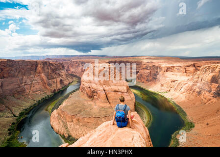 Young man sitting on a rock at Horseshoe Bend, bend of the Colorado River, King Bend, Glen Canyon National Recreation - Stock Photo