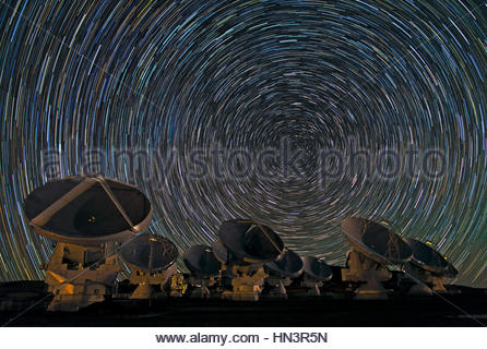 Long exposure of star trails around the south celestial pole and above the Atacama Large Millimeter/submillimeter - Stock Photo