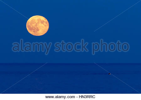 The full moon rises over the Atlantic Ocean and a small boat off the coast of Boston. - Stock Photo