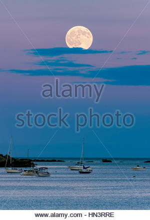 The full moon rises over the Atlantic Ocean and a small boats off the coast of Boston. - Stock Photo