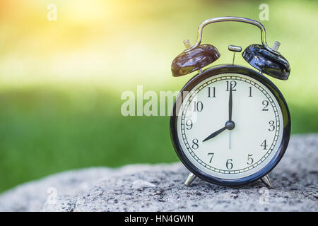clock in the green nature background, retro bell clock time at 8 o'clock. - Stock Photo