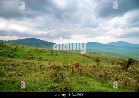 Scenic view in Tanzania with dramatic sky and small village ahead, depression near Ngorongoro crater - Stock Photo