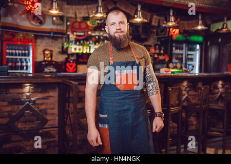 Bearded barman with tattoos and watches wearing an apron standing near the bar. - Stock Photo