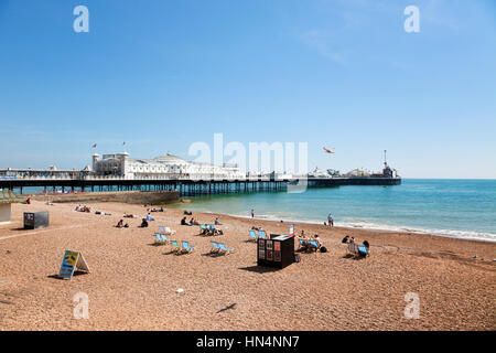 Brighton, Sussex, United Kingdom - May 16, 2014: Tourists relaxing on the beach next to the Brighton Pier from 1899. - Stock Photo