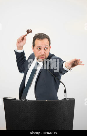 A male auctioneer in action holing a gavel during a live auction. - Stock Photo