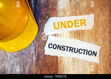 Under construction concept with protective yellow hard hat helmet on wooden desk - Stock Photo