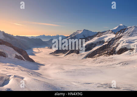 Sunrise over the Aletsch Glacier from Jungfraujoch in Switzerland on a clear morning. - Stock Photo