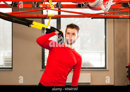 TRX training. Crossfit instructor at the gym doing TRX Excersise. Fitness man workout on the rings. Fitness man - Stock Photo