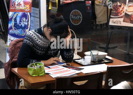 Young Japanese student studying and using smartphone, woman working in a bar with mobile phone. Hiroshima, Japan, - Stock Photo