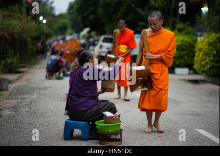 Buddhist monks receiving food from local people, Laos - Stock Photo