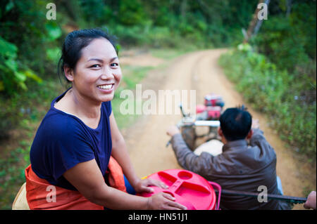 Lao woman riding on a tractor - Stock Photo