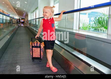 Happy little child with luggage stand on airport transit hall walkway moving to plane departure gate for waiting - Stock Photo