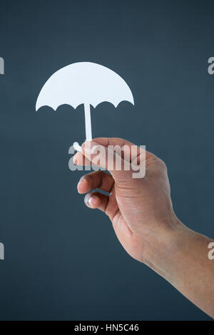 Hand of businessman holding paper cut out umbrella against grey background - Stock Photo