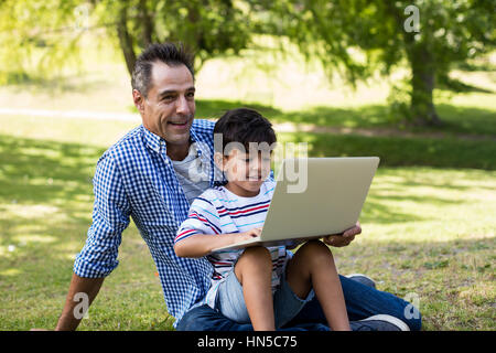 Boy sitting on his fathers lap and using laptop in park on a sunny day - Stock Photo