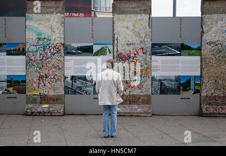 Berlin Germany. Person looking at Section of the Berlin Wall erected as a display. - Stock Photo