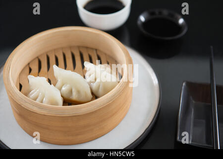 Close-up of steamed dumplings in bamboo steamer - Stock Photo