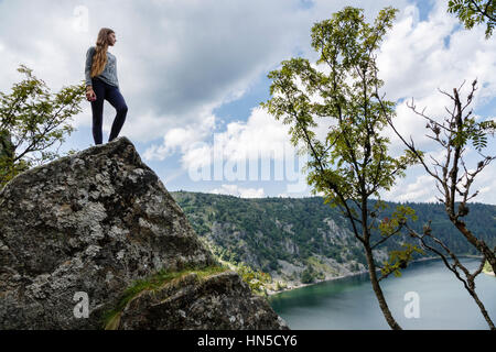 Girl admiring the view from Rocher Hans above Lac Blanc, Haut-Rhin, Alsace, France - Stock Photo