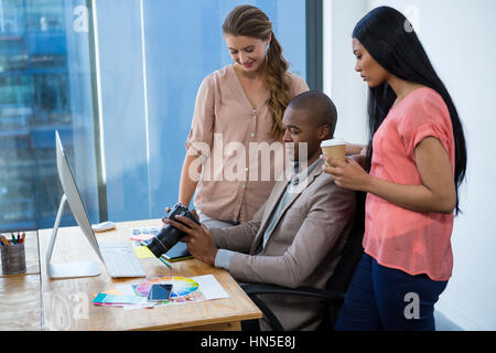Graphic designer reviewing photos in camera with colleagues in office - Stock Photo