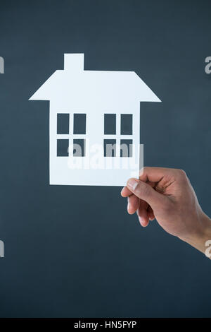 Hand of man holding paper cut out house on grey background - Stock Photo