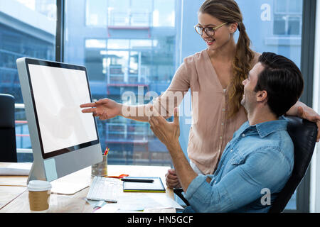 Graphic designer working at desk with colleague in office - Stock Photo