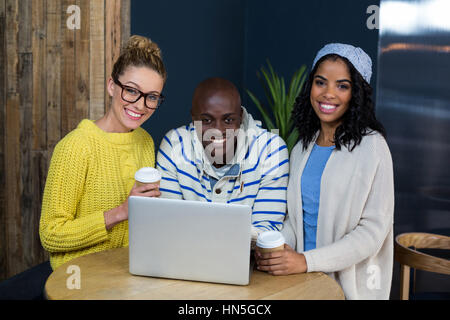 Portrait of happy friends using laptop while having coffee in café - Stock Photo