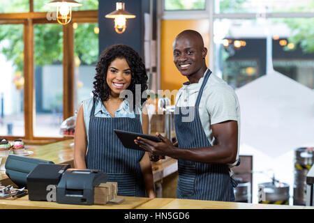 Portrait of smiling waiter and waitress using digital tablet at counter in cafe - Stock Photo